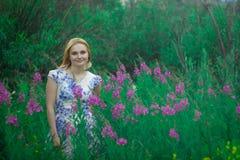 Muchacha roja que se coloca en un prado de la flor fotos de archivo