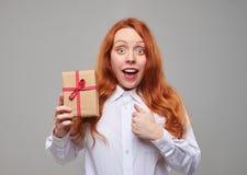 Muchacha roja sensible del pelo que sostiene una actual caja aislada Imágenes de archivo libres de regalías