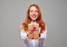 Muchacha roja sonriente del pelo que da la caja de regalo Foto de archivo libre de regalías