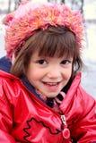 Muchacha roja vestida sonriente en el invierno Foto de archivo