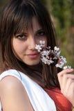 Muchacha romántica adolescente que lleva a cabo la rama del flor de la almendra Foto de archivo