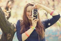 Muchacha romántica con la cámara cerca del árbol Fotografía de archivo