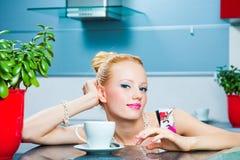 Muchacha romántica con la taza de café en el interior del ki Fotos de archivo