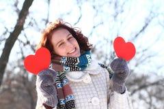 Muchacha romántica del invierno con dos corazones rojos al aire libre Fotografía de archivo
