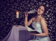 Muchacha romántica encantadora atractiva con el cuerpo hermoso que lee un libro y que escribe un poema y versos Imagen de archivo