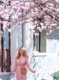 Muchacha romántica hermosa de la primavera en la situación del vestido de la moda en árboles florecientes de la magnolia fotografía de archivo