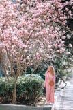 Muchacha romántica hermosa de la primavera en la situación del vestido de la moda en árboles florecientes de la magnolia imagen de archivo libre de regalías