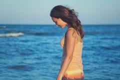 Muchacha romántica joven en la playa en la puesta del sol Imágenes de archivo libres de regalías