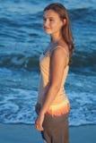 Muchacha romántica joven en la playa en la puesta del sol Imagen de archivo