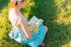 Muchacha romántica joven que lee un libro que se sienta en la hierba Imagen de archivo