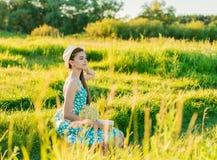 Muchacha romántica joven que lee un libro que se sienta en la hierba Fotografía de archivo libre de regalías
