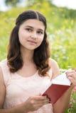 Muchacha romántica que lee un libro en la naturaleza Fotos de archivo libres de regalías