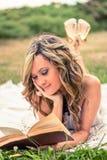 Muchacha romántica que lee un libro que se acuesta al aire libre Fotos de archivo