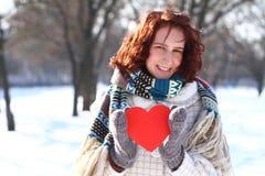 Muchacha romántica que lleva a cabo un corazón rojo en el fondo de un invierno Fotografía de archivo libre de regalías