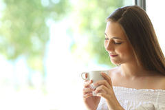 Muchacha romántica que piensa y que mira la taza de café Fotografía de archivo