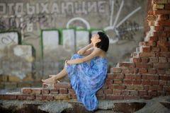 Muchacha romántica que se sienta en una pared de ladrillo Fotografía de archivo libre de regalías