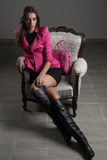 Muchacha rosada de la chaqueta en silla vieja imagen de archivo