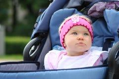 Muchacha rosada en sillón de ruedas azul Imágenes de archivo libres de regalías