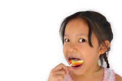 Muchacha rota asiática de los dientes y lollypop grande Imagen de archivo libre de regalías