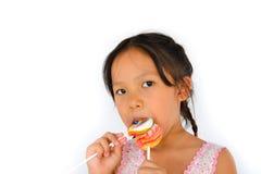 Muchacha rota asiática de los dientes y lollypop grande Imagenes de archivo