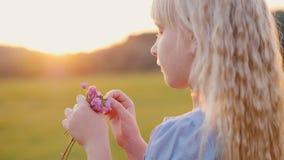 Muchacha rubia 6 años con un ramo de wildflowers Colocándose en el campo en la puesta del sol, vista lateral almacen de metraje de vídeo
