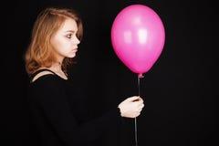 Muchacha rubia adolescente con el globo rosado sobre negro Imagen de archivo