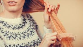 Muchacha rubia adolescente que cepilla su pelo con el peine Fotos de archivo