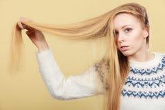 Muchacha rubia adolescente que cepilla su pelo con el peine Foto de archivo libre de regalías