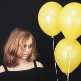 Muchacha rubia adolescente triste con los globos amarillos Imagen de archivo