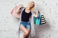 Muchacha rubia adorable contra la pared con compras Imagen de archivo