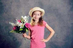 Muchacha rubia agradable con el sombrero de paja y el ramo de flores imagenes de archivo