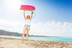 Muchacha rubia agradable en la playa con la tabla hawaiana Imagen de archivo libre de regalías