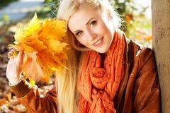 Muchacha rubia agradable en parque del otoño Foto de archivo