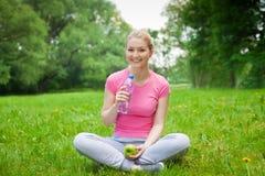 Muchacha rubia al aire libre en el parque con agua y la manzana Imagen de archivo libre de regalías