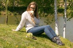 Muchacha rubia al aire libre en el parque con agua y la manzana en la hierba Foto de archivo