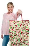 Muchacha rubia alegre que sostiene el bolso de compras en brazo outstretched Imagen de archivo libre de regalías