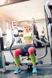 Muchacha rubia apuesta que ejercita en el gimnasio Fotografía de archivo