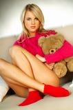 Muchacha rubia atractiva con el oso de peluche Fotos de archivo