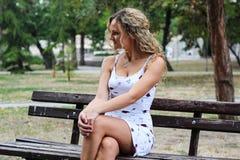 Muchacha rubia atractiva con el pelo rizado que se sienta en el banco en a Fotografía de archivo