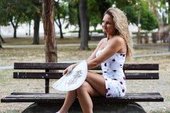 Muchacha rubia atractiva con el pelo rizado que se sienta en el banco en a Foto de archivo