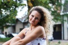 Muchacha rubia atractiva con el pelo rizado que se sienta en el banco en a Foto de archivo libre de regalías