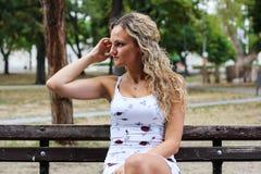 Muchacha rubia atractiva con el pelo rizado que se sienta en el banco en a Imagen de archivo