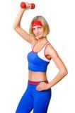 Muchacha rubia atractiva con pesa de gimnasia roja Imagen de archivo