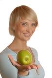 Muchacha rubia atractiva con una manzana Imagenes de archivo