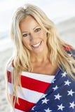 Muchacha rubia atractiva de la mujer en bandera americana en la playa Fotografía de archivo libre de regalías