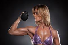 Muchacha rubia atractiva del culturista con pesas de gimnasia. Fotografía de archivo libre de regalías