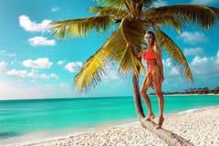 muchacha rubia atractiva en la playa con las palmas y el cielo azul imagen de archivo