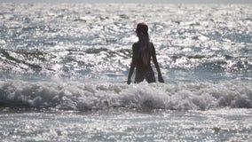 Muchacha rubia atractiva en ondas del mar metrajes
