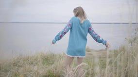 Muchacha rubia atractiva en vestido azul corto hermoso del verano con el baile del bordado en la hierba El río está en almacen de metraje de vídeo