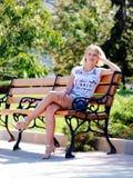 Muchacha rubia atractiva joven en parque del verano Foto de archivo